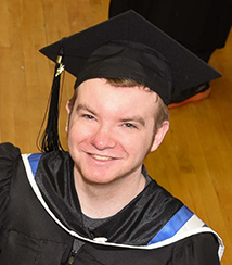 Ryan Linkletter smiling at camera, wearing graduation cap and gown