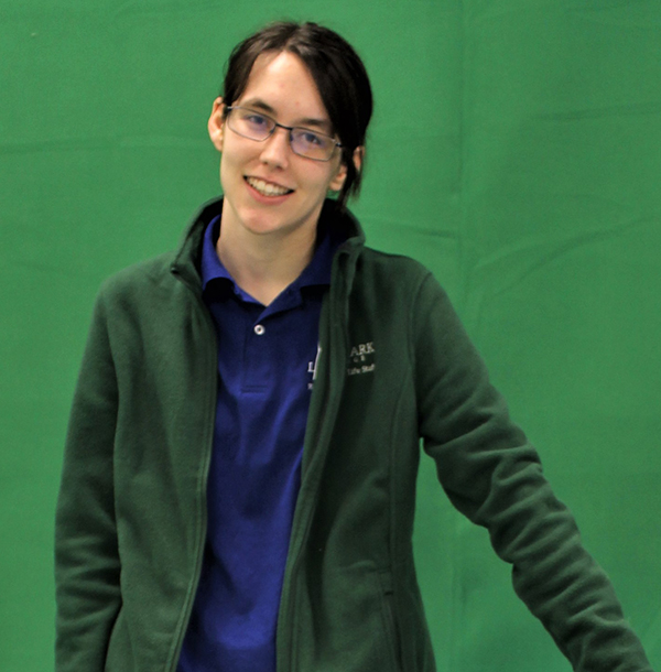 Female with dark hair tied back in pony with glasses, standing and smiling with green backdrop