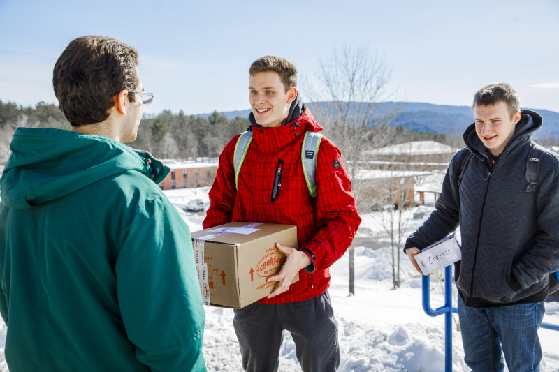 Two students hold boxes and smile while other student looks on, with snowy Landmark College campus in background