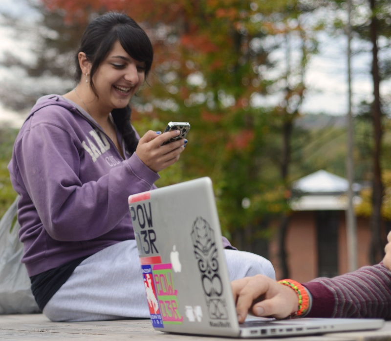 Student outdoors looking at cell phone