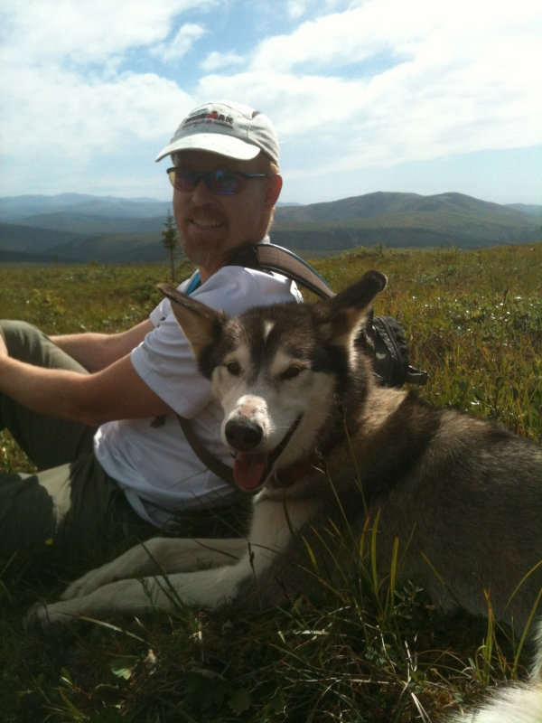 Brian Young with husky dog in foreground and mountains in background