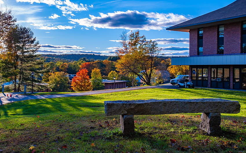 Landmark College Upper Campus stone bench overlooking lower campus and the autumn forest and hills in the background
